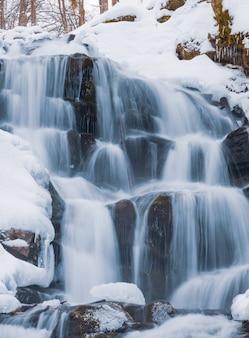 Piccola cascata di montagna di acqua ghiacciata scorre tra pietre bagnate ricoperte di neve bianca