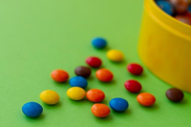 Piccole caramelle multicolore in confetto si affiancano a un barattolo giallo per caramelle