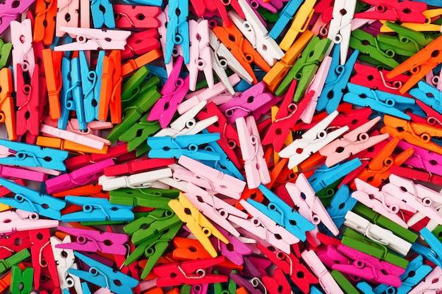 Piccole mollette multicolori come trama e sfondo a schermo intero. mollette decorative per la creatività.