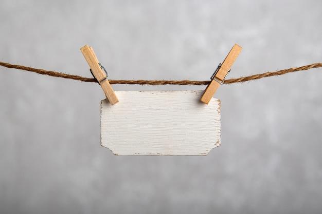 Piccola targhetta appesa con mollette su corda. segno bianco in bianco, piatto per un'iscrizione. copia spazio. posto per il testo.