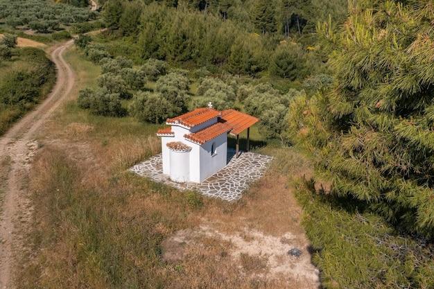 Piccola vecchia chiesa con pareti bianche e tetto di tegole in cima a una collina circondata da ulivi