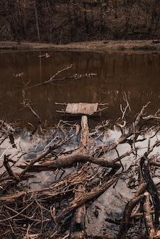 Un piccolo vecchio molo di legno distrutto sul fiume con i rami degli alberi gettati via
