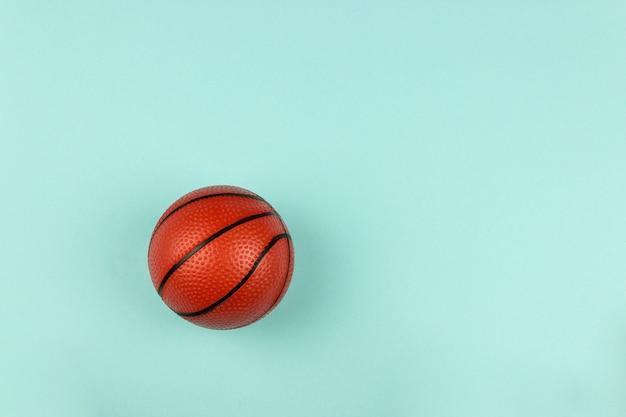 Piccola palla arancione per il gioco sportivo di basket su sfondo blu.