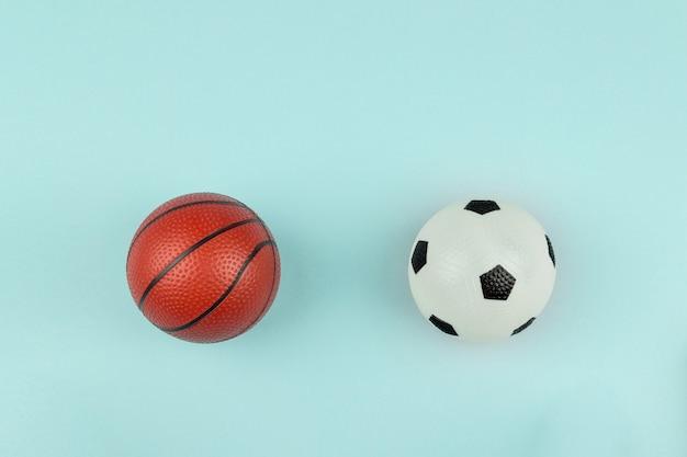 Piccola palla arancione e bianca per il gioco sportivo di basket e calcio su sfondo blu.