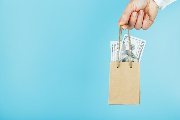 Un piccolo sacchetto di carta per aiuti finanziari e supporto fatto di carta a distanza con dollari usa su sfondo blu. il concetto di sostegno finanziario trascurabile negli affari,