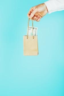 Piccolo sacchetto di carta in mano con dollari usa su uno sfondo blu. layout del modello di imballaggio con spazio per la copia, pubblicità.