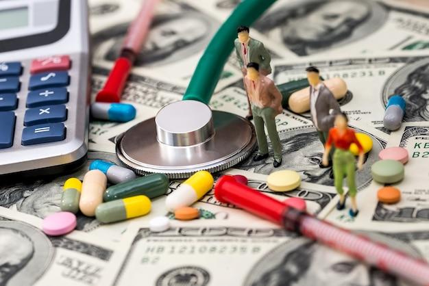 Piccole persone sul dollaro con pillole e stetoscopio