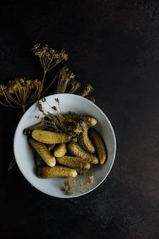 Piccoli cetrioli sottaceto in un piatto su uno sfondo scuro.