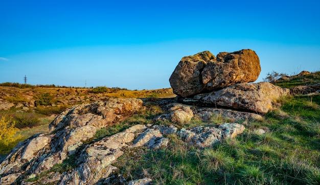 Un piccolo mucchio di vecchie pietre in un grande campo giallo-verde sullo sfondo di un cielo blu straordinariamente bello