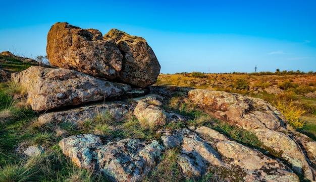 Un piccolo mucchio di vecchie pietre in un grande campo verde-giallo contro un cielo azzurro fantasticamente bello