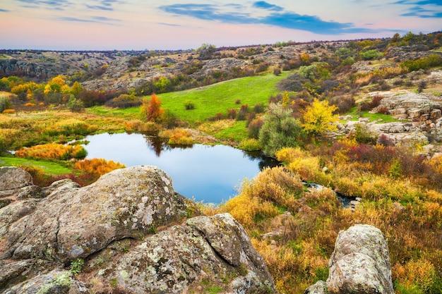 Un piccolo mucchio di pietre in un campo verde-giallo sullo sfondo del cielo nella bellissima ucraina