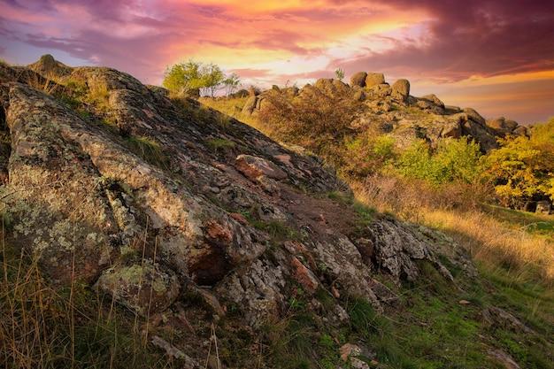 Un piccolo mucchio di pietre in un campo verde-giallo sullo sfondo di un cielo in ucraina