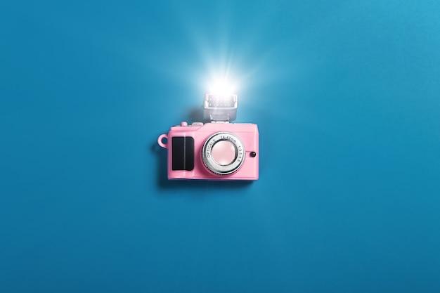 Piccola fotocamera rosa con flash su sfondo blu
