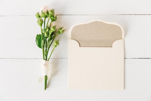 Piccole rose rosa con busta aperta in carta artigianalesfondo in legno bianco e piatto minimalista