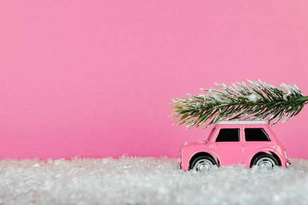 Piccola auto giocattolo rosa che trasportano albero di abete rosso su una strada innevata