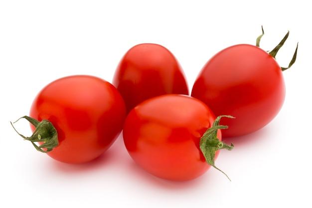 Piccoli pomodorini su una superficie bianca