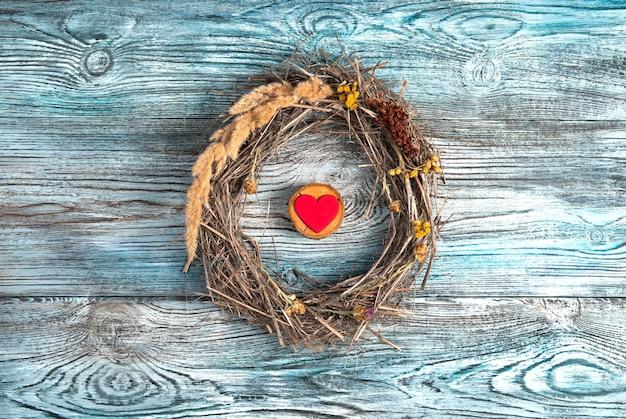 Un piccolo cuore rosso su un supporto di legno all'interno di una cornice di rami secchi ed erba su uno sfondo di legno.