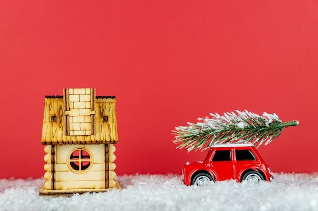 Piccola automobile rossa del giocattolo che trasporta l'albero di abete rosso su una strada della neve alla casa di legno