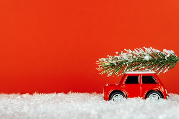 Piccola automobile rossa del giocattolo che trasportano albero di abete rosso su una strada innevata