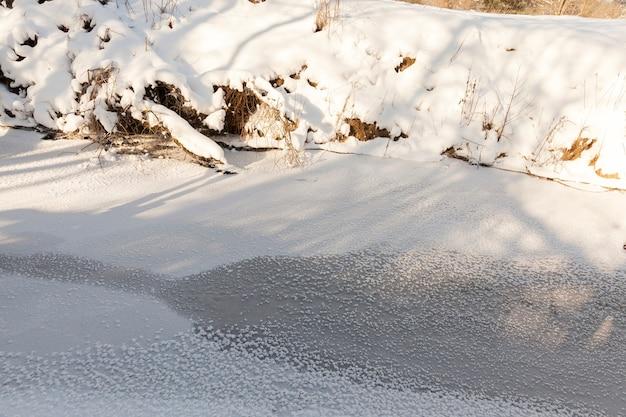 Un piccolo fiume la cui acqua è ghiacciata in inverno, un fiume ghiacciato durante le gelate invernali, neve e gelo in natura in inverno vicino a un fiume o a un lago