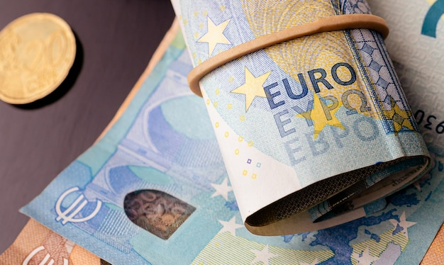 Un piccolo rotolo di banconote in euro su un tavolo scuro per l'economia dell'unione europea