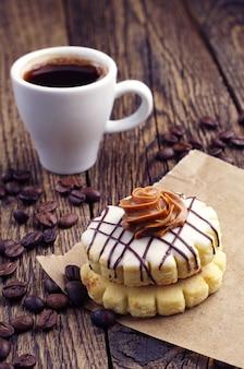 Piccola torta rotonda e tazza di caffè sul tavolo in legno vintage