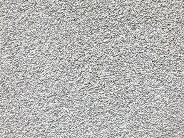 Piccola arenaria dalla trama del muro di sabbia o dallo sfondo del muro di sabbia. sfondo bianco pulito, la superficie sembra ruvida. forma di carta da parati. elemento di stampa grigio. spazio per testo o logo