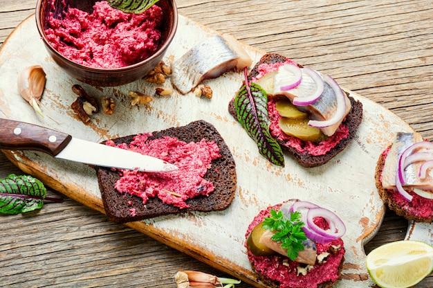 Piccoli tramezzini o bruschette con aringa salata, barbabietola e cipolle