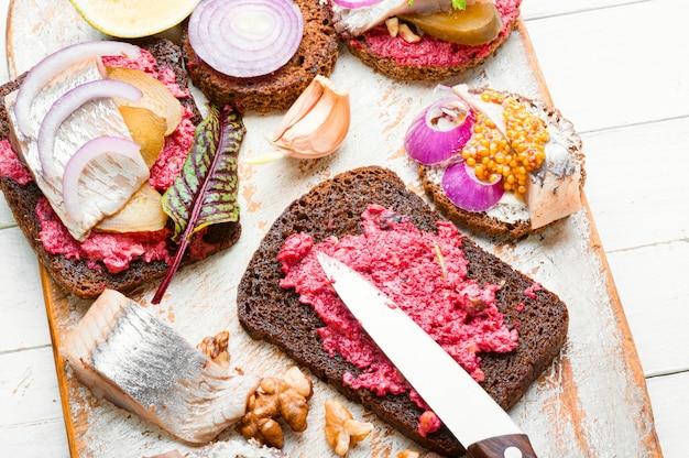 Piccoli tramezzini o bruschette con aringa salata e barbabietola.panino aperto con aringa salata