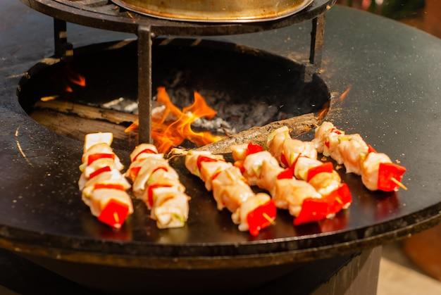 Piccolo satay di carne e verdure su spiedini di legno fritti su un braciere da vicino