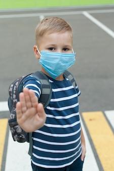 Un piccolo scolaro con una maschera durante uno scoppio del virus corona