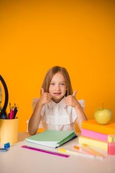 Una piccola studentessa in uniforme è seduta a un tavolo con materiale scolastico su uno sfondo giallo con un posto per il testo