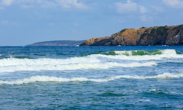 Piccola mareggiata al largo della costa rocciosa. serata panoramica dalla spiaggia.