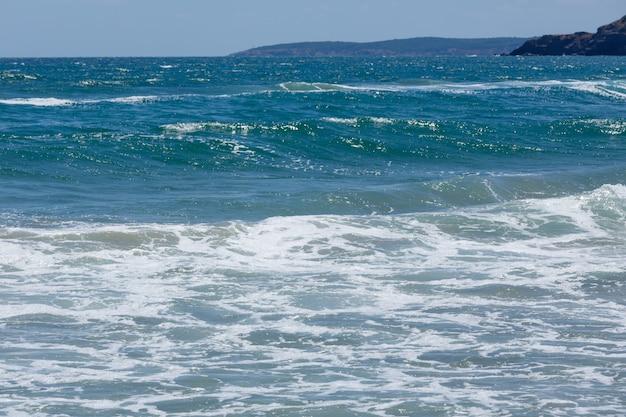 Piccola mareggiata al largo della costa rocciosa. scenico dalla spiaggia.