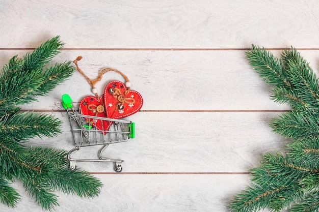 Piccolo carrello con doni e rami di abete su fondo in legno