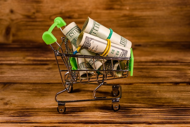 Piccolo carrello con banconote da cento dollari arrotolate su uno sfondo di legno