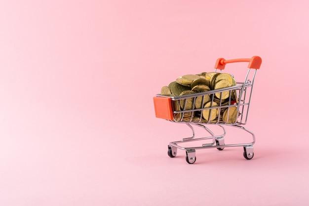Piccolo carrello della spesa pieno di monete d'oro su sfondo rosa chiaro.