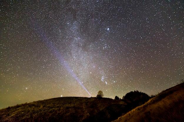 Piccola siluetta dell'uomo con la torcia elettrica sulla collina erbosa verde sotto il cielo stellato di estate blu scuro.
