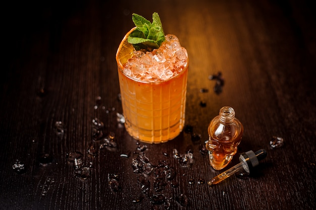 Piccola bottiglia a forma di teschio e cocktail all'arancia