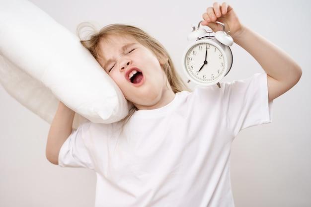 Una piccola ragazza assonnata abbraccia un cuscino e una sveglia su uno sfondo bianco. prime ascensioni dei bambini a scuola e all'asilo. biancheria da letto confortevole.