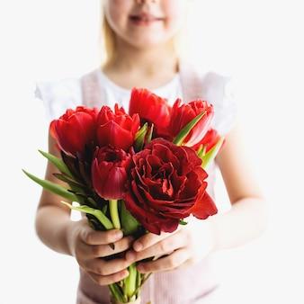 Piccola ragazza sorridente con bouquet di fiori di tulipano rosso. concetto di festa della mamma