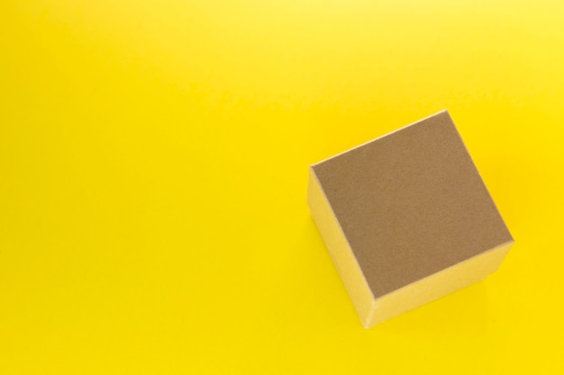 Piccola scatola di cartone quadrata su superficie gialla