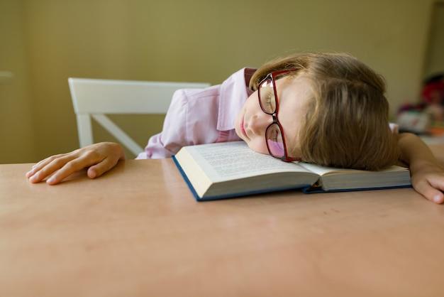 Piccolo studente con gli occhiali dorme su una scrivania