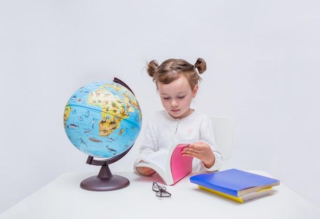 Piccolo studente si siede a un tavolo e legge un libro su un bianco isolato con spazio per il testo.
