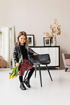 Una piccola ragazza elegante con una giacca di pelle nera e una gonna scozzese con un mazzo di tulipani è in piedi nella stanza.
