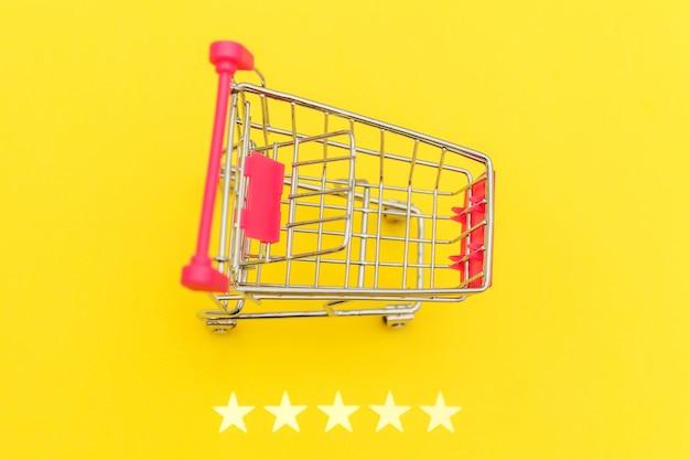 Carrello di spinta della piccola drogheria del supermercato per il giocattolo di compera con le ruote e una valutazione di 5 stelle isolata su fondo giallo. consumatore al dettaglio che acquista concetto online di valutazione e recensione.