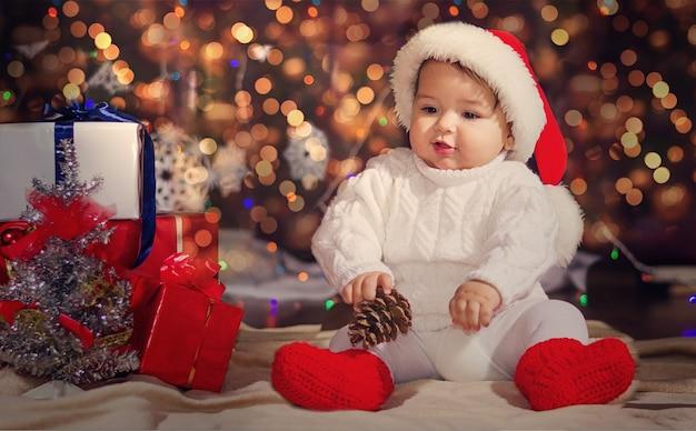 Piccolo bambino sorpreso in un cappello di babbo natale. ragazzo su una superficie ghirlande novoodney con scatole con doni e un nodulo in mano.