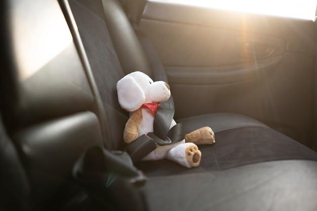 Un piccolo orsacchiotto protetto con cintura di sicurezza in auto, sicurezza in caso di incidente stradale