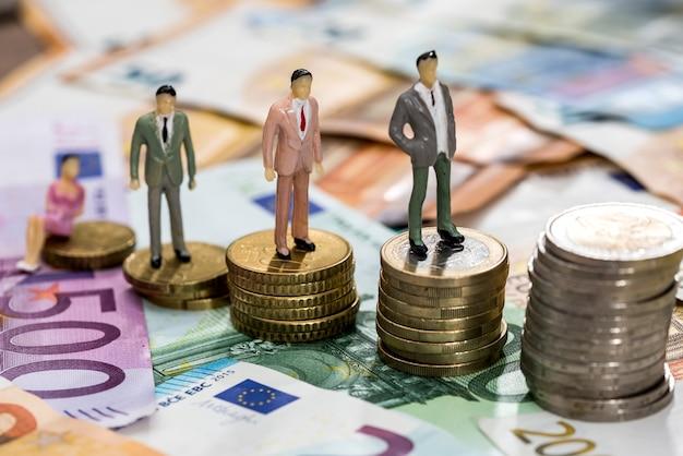Le persone di piccoli giocattoli sono sulle monete in euro e le banconote in euro Foto Premium