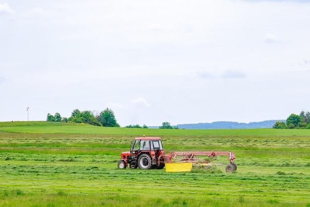 Un piccolo trattore con un rastrello rotante rastrella l'erba appena tagliata nel campo. lavoro agricolo